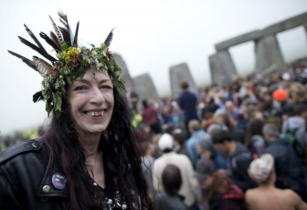 A woman takes part in the festivities at Stonehenge, which drew thousands of people.
