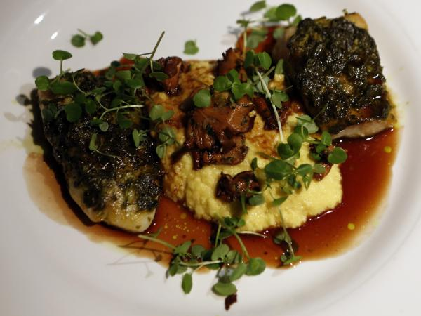 Fillets of chimichurri-crusted red snapper and tilapia, separated by fresh corn polenta.