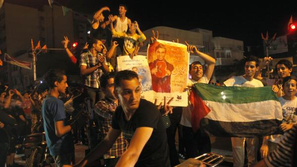 Palestinians dance with pictures of singer Mohammed Assaf as they celebrate his <em>Arab Idol</em> victory along the streets of Gaza City Saturday.