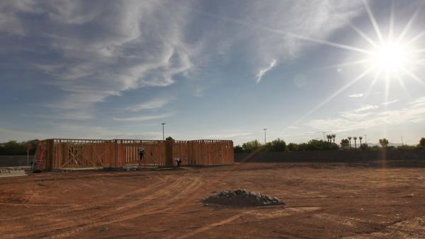 Workers frame a home in Gilbert, Ariz., near Phoenix, in July 2012. Developers are buying up half-built and vacated subdivisions amid renewed demand for housing.