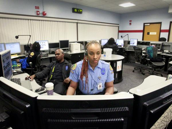 Miami Police Department dispatcher Shekita Johnson and officer Ernest Lawrence staff the boards at Miami's Communications Unit. Call-takers in the unit screen the 911 calls, then send them to dispatchers.