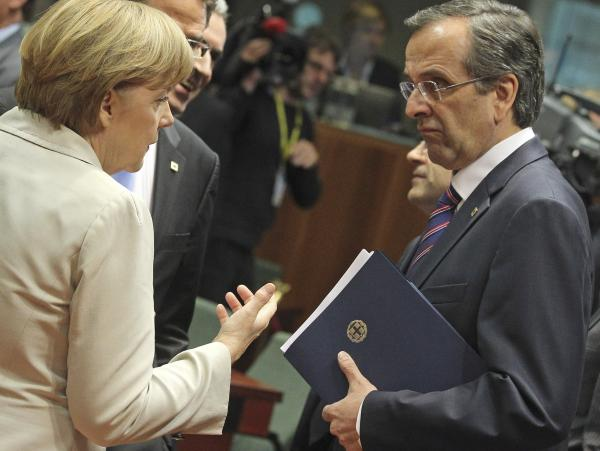 Greek Prime Minister Antonis Samaras speaks with German Chancellor Angela Merkel during an EU summit in Brussels last week. Samaras began his term by refusing to negotiate with with EU leaders, but now calls Merkel an ally.