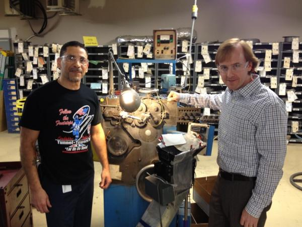 Juan Delgado (left) and Steve Kempf of Brooklyn's Lee Spring company stand with a 50-year-old coiling machine, still in use today.