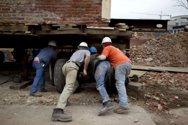 Workers position platforms with tractor-trailer-size tires under a building.