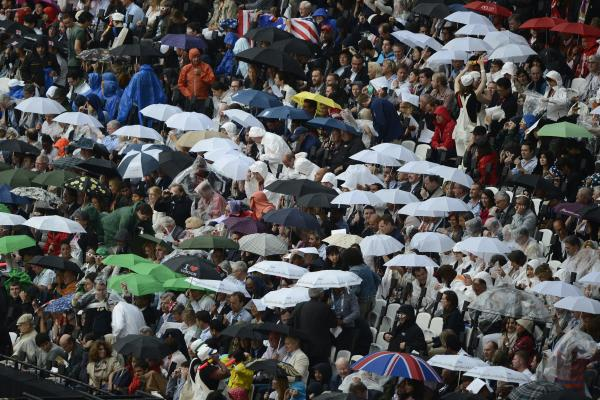 Rain falls on spectators in the Olympic stadium.