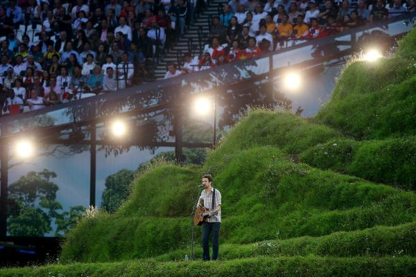 Guitarist Frank Turner performs on the hillside.