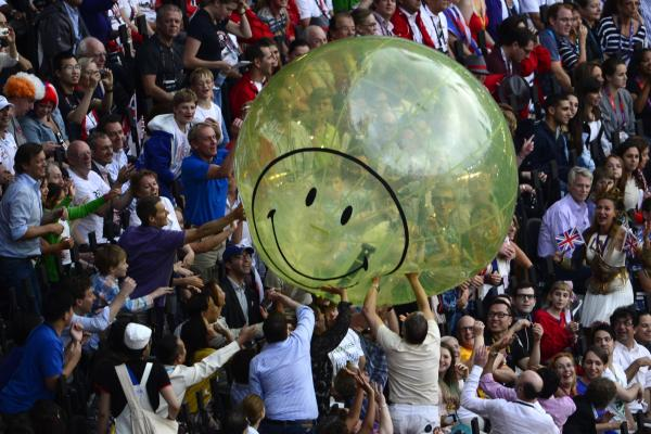 Spectators play with a giant balloon at the Olympic stadium.