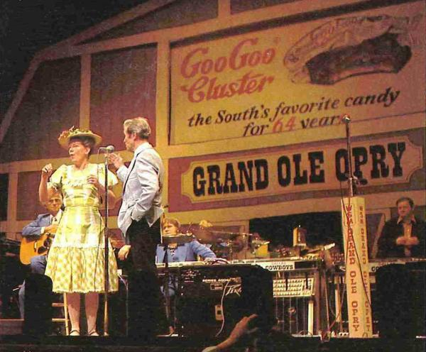 Minnie Pearl and Roy Acuff perform in front of a Goo Goo Cluster advertisement at the Grand Ole Opry, circa 1976. Coincidentally, Pearl's 100th birthday is also in October.