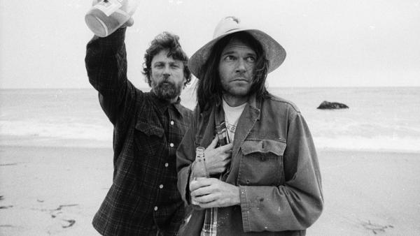 Neil Young (right) with book art director and friend Gary Burden, on the beach in Malibu, 1975.