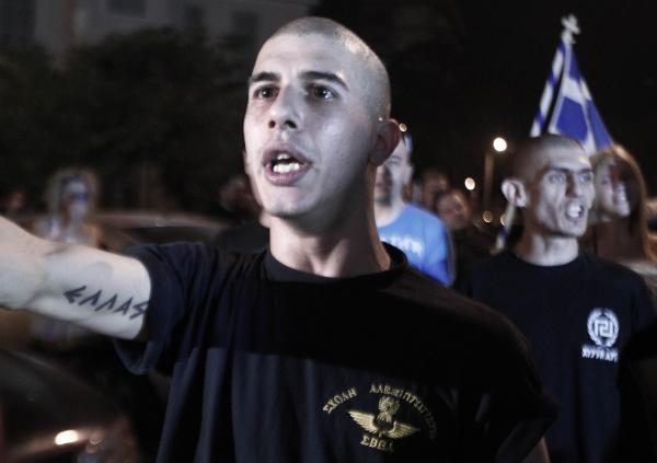 "Supporters of Golden Dawn celebrate the results of the elections outside of their Thessaloniki headquarters in June. The tattoo reads ""Greece."""