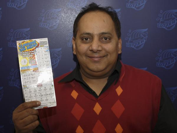 Urooj Khan poses with a winning lottery ticket. He died after winning a $1 million lottery in Chicago. Forensic pathologists at first said Khan died of natural causes, but that ruling was later changed to death by cyanide poisoning.