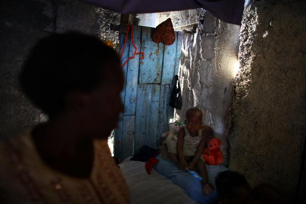 Bibeta Louissaint (left) stands in her makeshift shack with her 2-year-old son, Sebastian, in the Fort National neighborhood of Port-au-Prince. This area was home to many people living in the camps around the national palace. Louissaint received a rental subsidy last year to move.