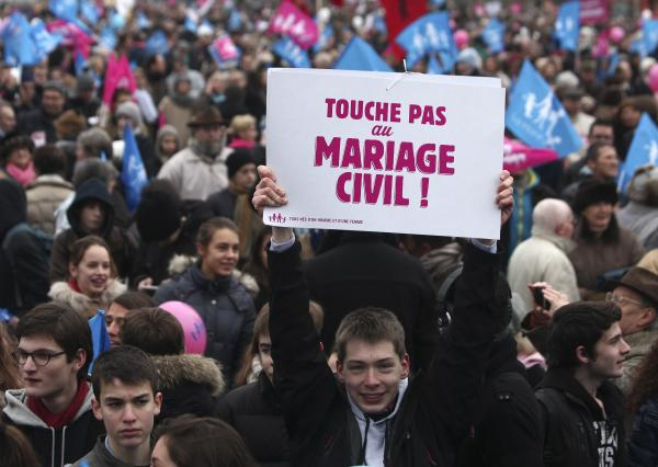 "A boy holds a poster reading ""Do not touch the civil marriage"" during a demonstration in Paris on Sunday as thousands of protesters mobilized against the French president's plan to legalize gay marriage."
