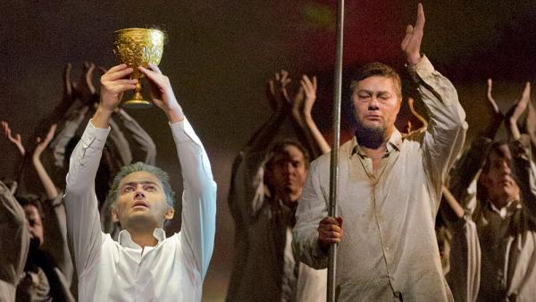 Parsifal (Jonas Kaufmann) lifts the Holy Grail as Gurnemanz (Rene Pape) looks on, in a recent Metropolitan Opera production of Wagner's final opera, <em>Parsifal</em>.