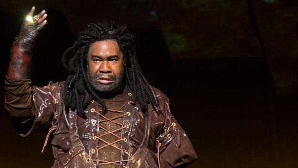Eric Owens plays the greedy dwarf Alberich, displaying his golden ring, in Wagner's <em>Das Rheingold</em>.