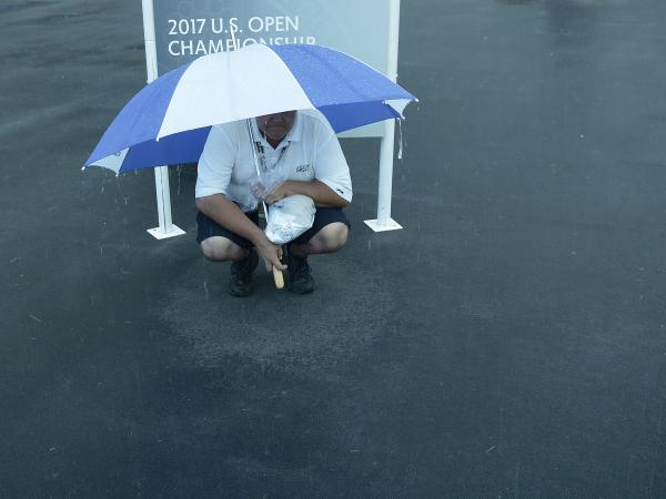 A man finds some shelter from the rain Thursday at the U.S. Open, which is being played at Merion Golf Club in Ardmore, Pa.