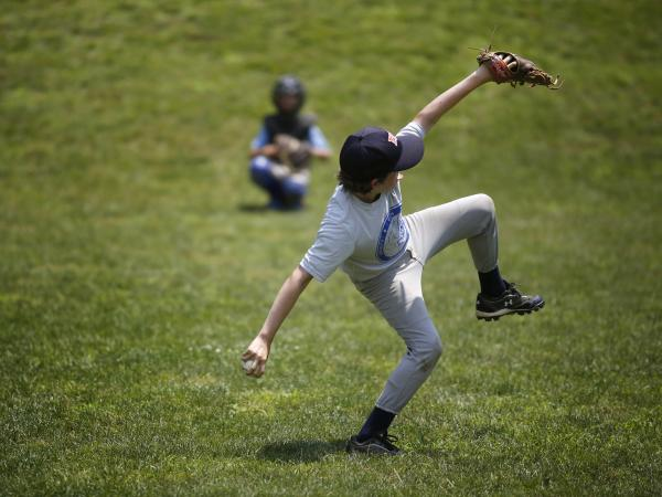 Harry Kaplan practices pitching during Home Run Baseball Camp at Friendship Recreation Center in June. Kaplan's arm is stretched long and toward the ground as his hips are faced away from the catcher. A chimp, in contrast, could never throw a fastball.