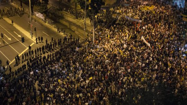"Protesters gather near a line of security blocking a road that leads to Maracana stadium in Rio de Janeiro, Brazil, on Sunday. <a href=""http://n.pr/19Y62Yz"">Anti-government protesters</a> marched near the soccer stadium before a major international match, venting their anger about the billions of dollars the government is spending on major sporting events rather than on public services."