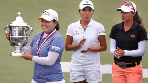 Inbee Park holds up the U.S. Women's Open trophy after her four-stroke victory in front of I.K. Kim of South Korea (center) and low amateur Casie Cathrea (right) at Sebonack Golf Club on Sunday in Southampton, New York. Park has won three consecutive major titles.