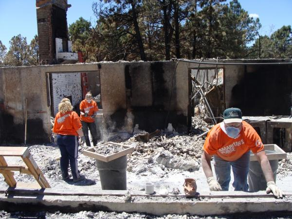 Samaritan's Purse volunteers work in a house. (Megan Verlee/Colorado Public Radio)