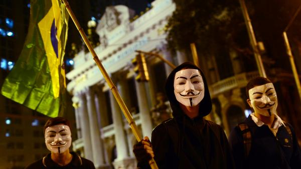 "<strong><a href=""http://www.npr.org/blogs/parallels/2013/06/18/193101142/with-inspiration-from-turkey-brazil-discovers-mass-protests"">Rio de Janeiro</a>:</strong> Demonstrators wearing Guy Fawkes masks and waving a Brazilian national flag march in downtown Rio on June 17 against higher public transportation fares and the use of public funds to finance international soccer tournaments."