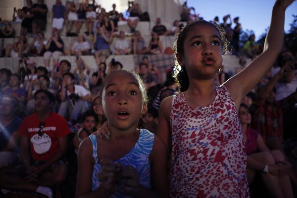 Emanuyani Yamni (left) and her sister Kaiar, both of Rochester, N.Y., enjoy the fireworks display over the reflecting pool from the Lincoln Memorial on the Fourth of July.