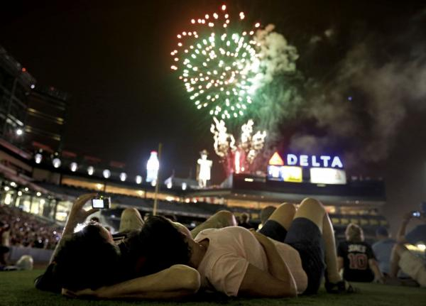 Bill Sandidge, left, and Nancy Koughan, of Decatur, Ga., watch a fireworks display on the field following a baseball game between the Chicago Cubs and the Atlanta Braves, Wednesday, July 4, 2012, in Atlanta. (David Goldman/AP)
