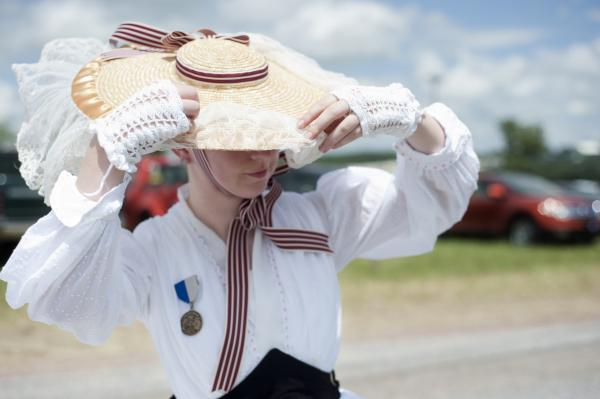 Emily Kelley, of Michigan, steadies her hat in the breeze. Kelley's interests were both history and fashion; a professor at Western Michigan University inspired several students to participate.