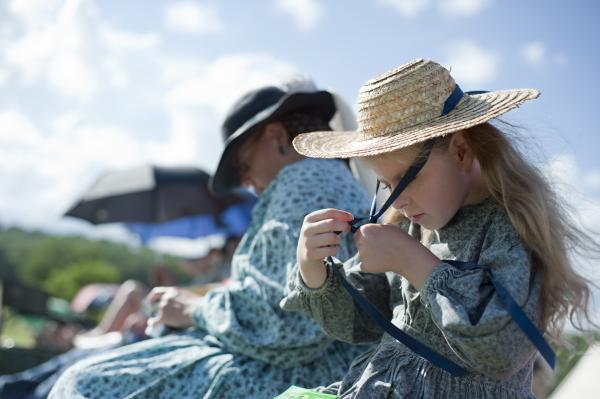 Mackenna Meek (right), 8, of Ohio, sits along the battlefield sidelines as her father marches in as a soldier in the Union Army.