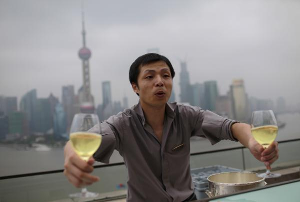 A waiter delivers glasses of wine to guests at a luxury hotel bar near the Bund in Shanghai, on Sept. 8, 2012.