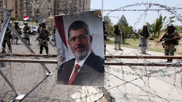 A poster showing ousted Egyptian President Mohammed Morsi was hanging on barbed wire outside the headquarters of the Republican Guard in Cairo on Saturday. On the other side, guards stood watch.