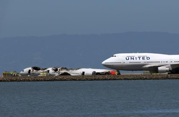 A United Airlines plane taxis on the runway with the Asiana Airlines plane in the background. After initially halting all flights, the airport slowly cleared the way for some flights.