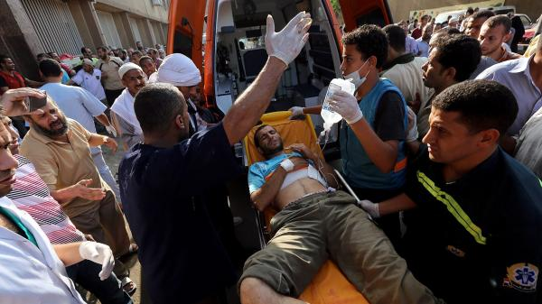 A wounded man is helped from the scene Monday in Cairo after shots were fired during a protest against the ouster of President Mohammed Morsi.