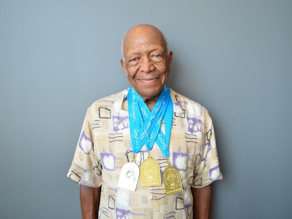 Swimmer John Tatum proudly wears his gold medals from the National Senior Olympics.