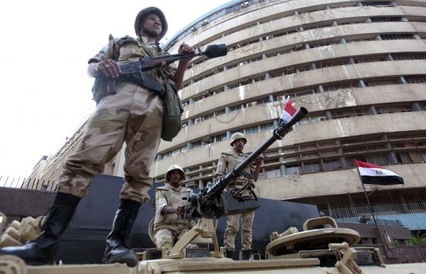 Soldiers stand on an armored personnel carrier positioned outside the state-run television station in Cairo, on July 6.