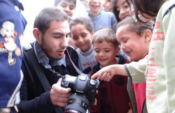 Syrian citizen journalist Fidaa al-Baali is pictured with his camera and a group of children. (Activists News Association/Facebook)