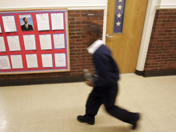 A student of the Barack Obama elementary school in Hempstead, N.Y. walks past a board displaying student essays on the president during the official name changing ceremony in 2009.