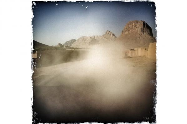 """Dust rises behind a convoy traveling down a dusty road near Kandahar. Soldiers refer to their backside as """"their six"""" — as in 6 o'clock: or, when facing ahead at 12, the area that's behind."""