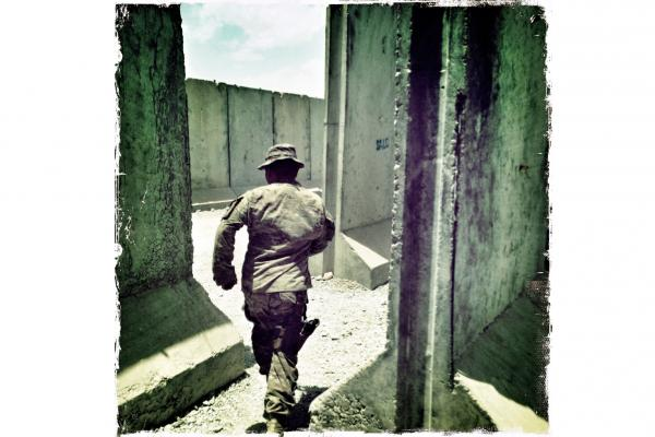 A soldier runs through a series of blastproof T-barrier walls in southern Afghanistan. In the event of a mortar or rocket attack, the walls help deflect or limit the area of collateral damage from the impact zone.