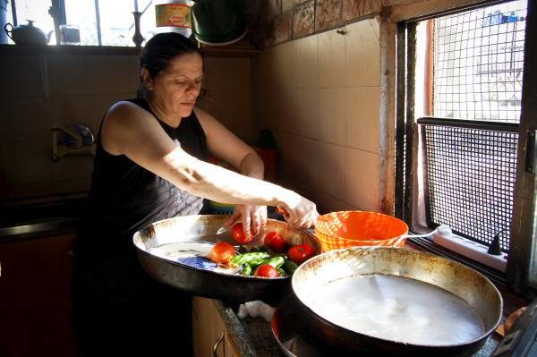 In the kitchen of her Old City apartment, Outteineh starts a Middle Eastern salad with tomatoes and cucumbers.