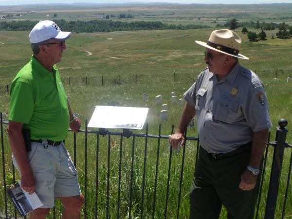 Seasonal Ranger Mike Donahue (right) discuses the Battle of Little Bighorn with Jon Jones atop Custer Hill.