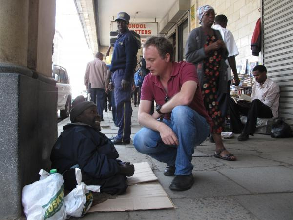 "Richard Crompton stops on the street to talk to ""George,"" a local supplicant and an inspiration for one of the characters in Crompton's first crime novel. Crompton says many of his characters are amalgams of people he met as a Nairobi journalist and resident."