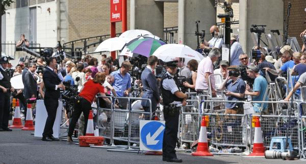 A British police officer, backdropped by members of the media, stands outside St. Mary's Hospital exclusive Lindo Wing in London, Monday, July 22, 2013. (Lefteris Pitarakis/AP)