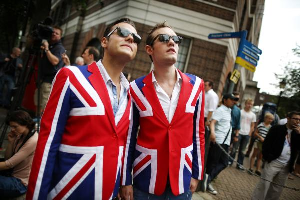 Men wearing Union Jack blazers wait for a glimpse of the duchess and her son at St. Mary's.