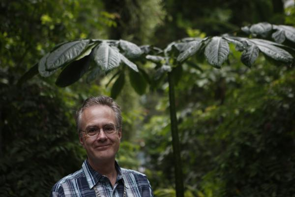 Kyle Wallick, a botanist with the U.S. Botanic Garden, stands by a nonblooming corpse flower.