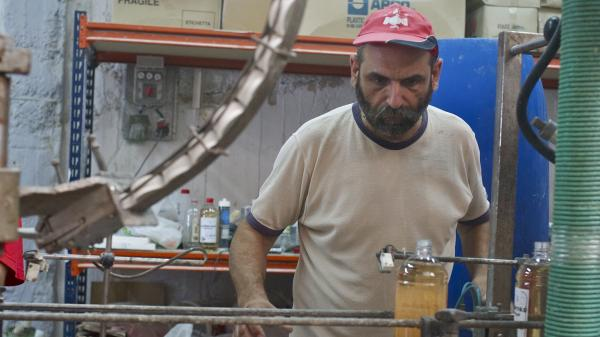 Makis Anagnostou, a worker and union leader, bottles lavender-scented fabric softener at VIO.ME, a former tile materials factory that went bust and has been revived by its staff as a collective making environmentally-friendly detergent.
