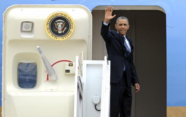 President Barack Obama waves as he boards Air Force One at Andrews Air Force Base, Md., Wednesday, July 24, 2013. Obama is traveling to Knox College in Galesburg, Ill., to kick off a series of speeches that will lay out his vision for rebuilding the economy. (Cliff Owen/AP)