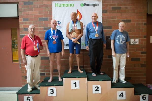 Johnston stands at the top of the podium for the 100-yard freestyle 80-to-84 age group awards at the Cleveland State University Natatorium on Wednesday. Graham and Peter Vandijk (second place) have been swimming against each other for 40 years.