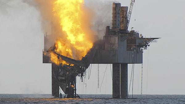 In this Wednesday, July 24, 2013 photo released by the U.S. Coast Guard, abatement efforts underway near Hercules 265 Rig where fire has caused collapse of the drill floor and derrick following an explosion Tuesday night. (U.S. Coast Guard via AP)