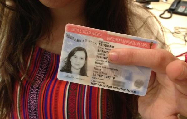 Renata Teodoro holds up her U.S. employment authorization card. (Here & Now)